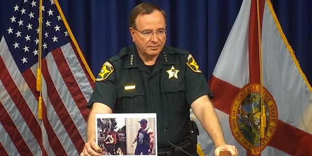 In a Sept. 9, 2021, briefing, Polk County Sheriff Grady Judd holds photos of Bryan Riley, who is accused of killing four people in Lakeland, Florida.