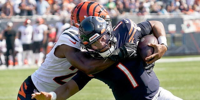 Chicago Bears quarterback Justin Fields (1) carries the ball and is tackled by Cincinnati Bengals cornerback Chidobe Awuzie during the second half of an NFL football game Sunday, Sett. 19, 2021, a Chicago.