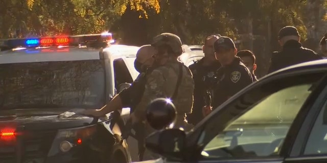 Authorities are seen in Oakland, Calif., on Wednesday. Police said one officer was shot by a suspect who later barricaded themselves in a building. (KTVU)