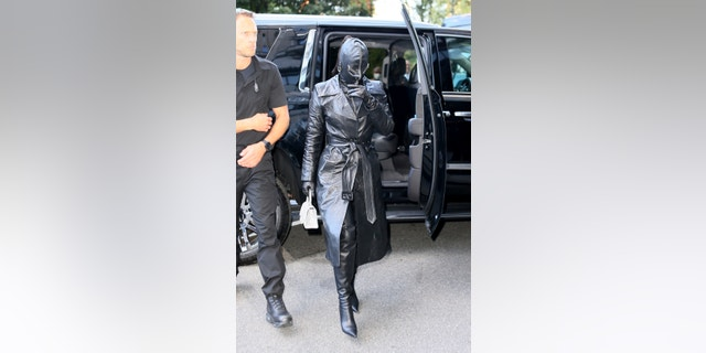 Kim Kardashian covers herself in leather from head to toe as she checks into the Ritz Carlton ahead of the Met Gala in New York.