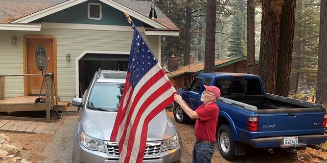 Bill Roberts rolls up an American flag in front of his house in South Lake Tahoe, Calif., last Tuesday -- a day after the city was ordered to evacuate because of the approaching Caldor Fire.