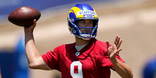 In this June 4, 2021, file photo, Los Angeles Rams quarterback Matthew Stafford passes during an NFL football practice in Thousand Oaks, Calif. With trips to the Super Bowl still in their recent memories, the Rams and the San Francisco 49ers made the decision this offseason that they needed more dynamic quarterback play to remain contenders in the long run. That led both NFC West rivals to make aggressive moves, trading multiple first-round picks to bring Stafford to Los Angeles and rookie Trey Lance to San Francisco. (AP Photo/Mark J. Terrill, File)