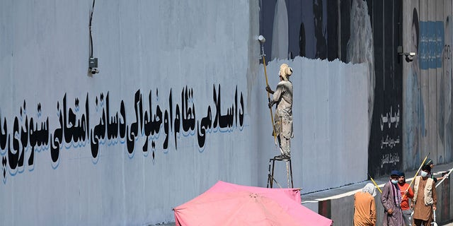 """A man paints over murals on a concrete wall with a message reading """"For an Islamic system and independence, you have to go through tests and stay patient"""", in Kabul."""