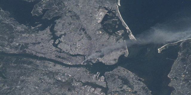 """Visible from space, a smoke plume rises from the Manhattan area after two planes crashed into the towers of the World Trade Center. This photo was taken of metropolitan New York City (and other parts of New York as well as New Jersey) the morning of September 11, 2001. """"Our prayers and thoughts go out to all the people there, and everywhere else,"""" said Station Commander Frank Culbertson of Expedition 3, after the terrorists' attacks."""