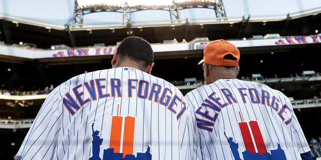 New York Mets fans wear jerseys to remember the 20th anniversary of the 9/11 terrorist attacks before a baseball game against the New York Yankees on Saturday, 九月. 11, 2021, 在纽约. (AP Photo/Adam Hunger)