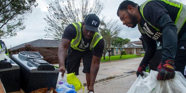 Elmor Garcia and Bruce Hayes, left, of IV Waste, pick up trash and storm debris following Hurricane Ida in Kenner, La., Monday, Sept. 6, 2021.
