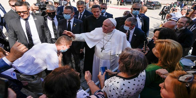 Pope Francis blesses an unidentified man as he greets the crowd while leaving the Cathedral of Saint Martin, in Bratislava, Slovakia, on Monday. (AP)