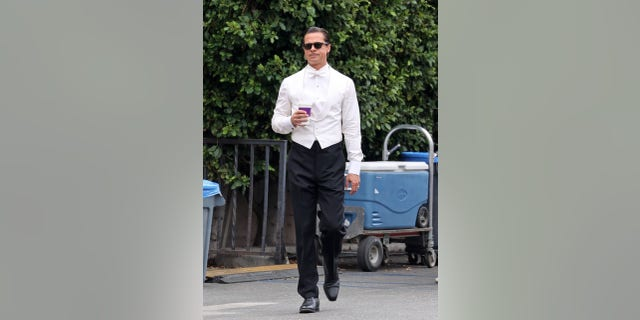 Brad Pitt filming sips on a coffee as he gets back to work on his latest film 'Babylon.' Brad looked dapper in a tuxedo outfit for today's scenes. Pitt stepped out briefly while filming an interior party scene for which he was dressed to the nines.
