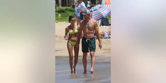 Justin Hartley and Sofia Pernas put their fit bods on display during a beach day stroll in Hawaii. The 44-year-old 'This is Us' star looked buff and was seen holding hands and laughing with Sofia, 32  as they took a stroll along the beach. Sofia wore a neon-colored two-piece and was seen carrying a drink.