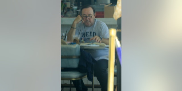 Spacey was seen reading from a book as he sat alone eating his lunch.
