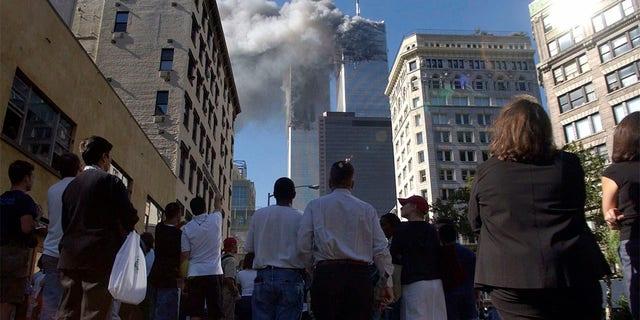 Pedestrians in lower Manhattan watch smoke billow from New York's World Trade Center on Tuesday, 9/11/01.