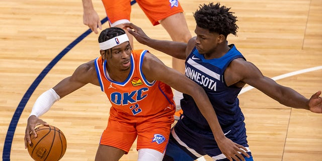 Oklahoma City Thunder guard Shai Gilgeous-Alexander (2) dribbles the ball as Minnesota Timberwolves forward Anthony Edwards (1) plays defense in the second half at Target Center.