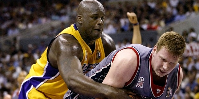 Los Angeles Lakers' Shaquille O'Neal (L) reaches from behind to latch onto the ball and New Jersey Nets' Todd MacCulloch during Game 1 of the NBA Finals June 5, 2002 in Los Angeles.