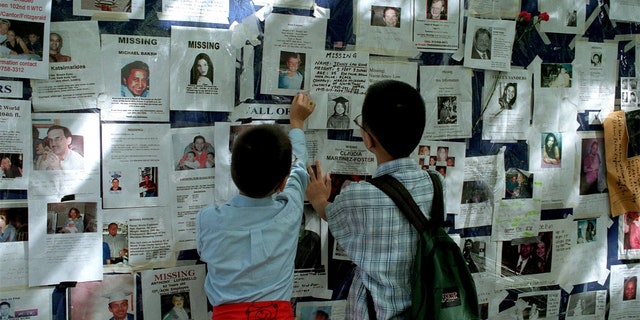 Two boys look at a poster of missing people outside Bellevue Hospital in the week after 9/11/01.