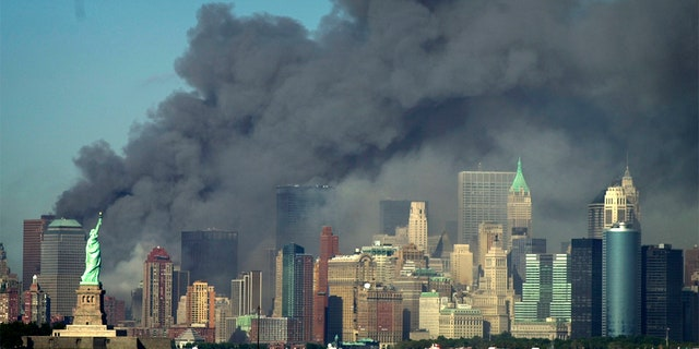 Thick smoke billows into the sky from the area behind the Statue of Liberty, lower left, where the World Trade Center was, on Tuesday, 9/11/01.