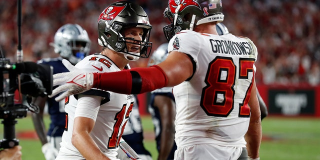 Tampa Bay Buccaneers quarterback Tom Brady (12) celebrates with tight end Rob Gronkowski (87) after Gronkowski caught a 2-yard touchdown pass during the first half of an NFL football game Thursday, Sept. 9, 2021, in Tampa, Fla. (AP Photo/Scott Audette)
