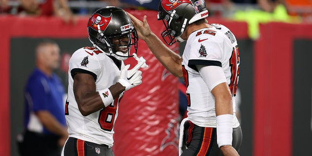 Tampa Bay Buccaneers quarterback Tom Brady (12) celebrates with wide receiver Antonio Brown (81) after Brown caught a touchdown pass against the Dallas Cowboys during the first half of an NFL football game Thursday, Sept. 9, 2021, in Tampa, Fla. (AP Photo/Mark LoMoglio)