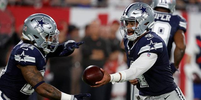 Dallas Cowboys quarterback Dak Prescott (4) hands off to running back Ezekiel Elliott (21) during the first half of an NFL football game against the Tampa Bay Buccaneers Thursday, Sept. 9, 2021, in Tampa, Fla. (AP Photo/Scott Audette)