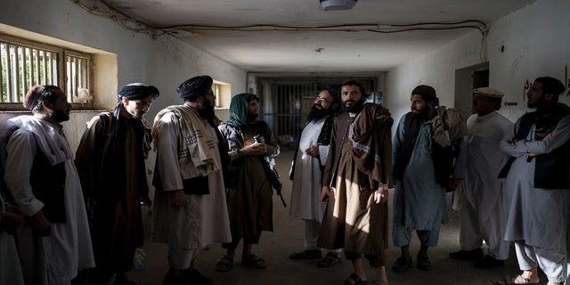 तालिबान लड़ाके, कुछ पूर्व कैदी, सोमवार को अफगानिस्तान के काबुल में पुल-ए-चरखी जेल के एक खाली इलाके में चैट करते हैं।