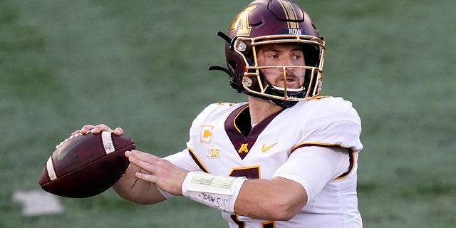 In this file photo from Nov. 7, 2020, Minnesota quarterback Tanner Morgan returns to pitch during the first half of an NCAA college football game against Illinois in Champaign, Illinois.  (AP Photo / Charles Rex Arbogast, File)