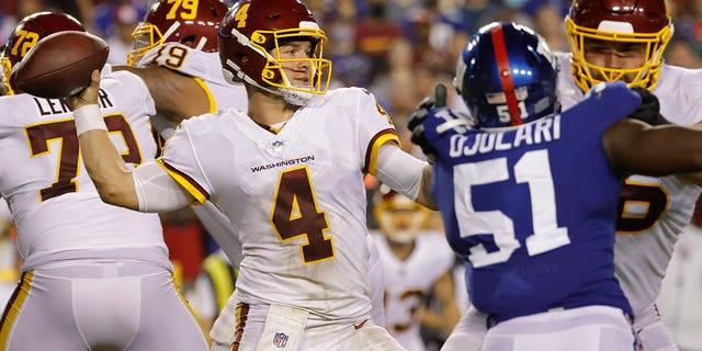 Washington Football Team quarterback Taylor Heinicke (4) passes the ball as New York Giants linebacker Azeez Ojulari (51) defends in the fourth quarter at FedExField.