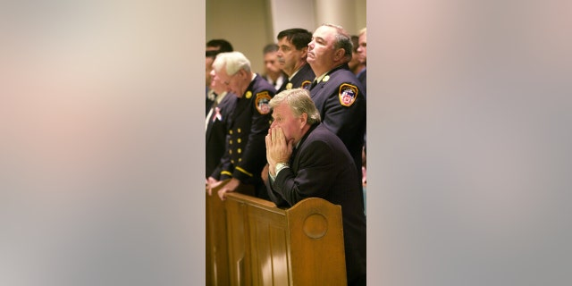 Then-Fire Commissioner Thomas Von Essen kneels at a memorial service for Firefighter Gregory Saucedo of Ladder Co. 5, a victim of the World Trade Center disaster, at Mary Queen of Heaven Catholic Church in Brooklyn.