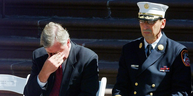 New York City Fire Commissioner Thomas Von Essen, left, rubs his eyes while then-New York City Mayor Rudolph Giuliani spoke at an NYFD promotions ceremony near NYFD headquarters in Brooklyn, New York, on Sept. 16, 2001.