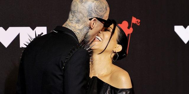 Travis Barker and Kourtney Kardashian share a kiss on the 2021 MTV Video Music Awards red carpet.