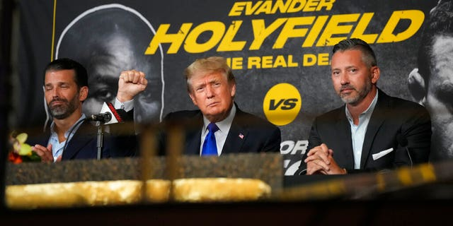 Former President Donald Trump, center, salutes cheering fans and he and son Donald Trump Jr., left, prepare to provide commentary for a boxing event headlined by a bout between former heavyweight champ Evander Holyfield and former MMA star Vitor Belfort, Saturday, Sept. 11, 2021, in Hollywood, Fla. (AP Photo/Rebecca Blackwell)