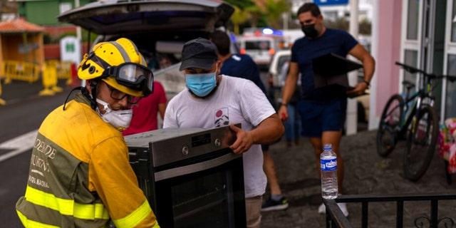 Жители вывозят вещи из своих домов во время потока лавы из извергающегося вулкана, когда их эвакуируют из своей деревни в Лос-Льянос, на острове Ла-Пальма на Канарских островах, Испания, среда, 22 сентября 2021 года.