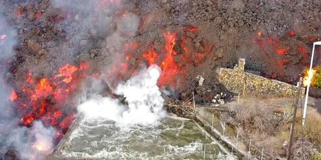 Горячая лава достигает Бальсы, обычно используемой для орошения, после извержения вулкана на острове Ла-Пальма на Канарских островах, Испания, в понедельник, 20 сентября 2021 года.
