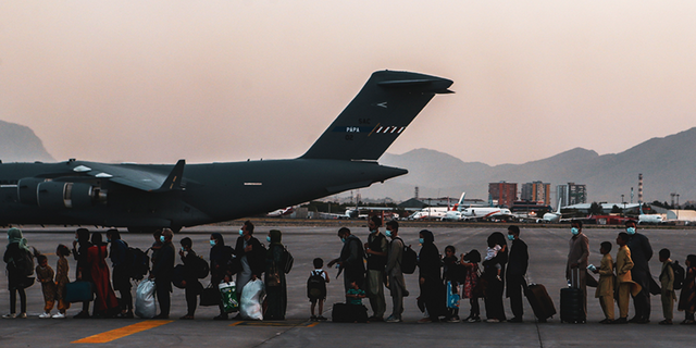 vacuees wait to board a Boeing C-17 Globemaster III during an evacuation at Hamid Karzai International Airport, Kabul, Afghanistan, Aug. 23. U.S. service members are assisting the Department of State with a Non-combatant Evacuation Operation (NEO) in Afghanistan. (U.S. Marine Corps photo by Sgt. Isaiah Campbell)