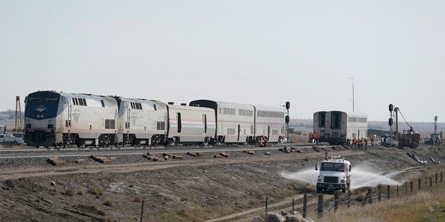 Một chiếc xe tải chở nước chạy trên đường, thứ Hai, ngày 27 tháng 9 năm 2021, bên cạnh một đoàn tàu Amtrak trật bánh hôm thứ Bảy, gần Joplin, Mont., Khiến ba người thiệt mạng và những người khác bị thương.