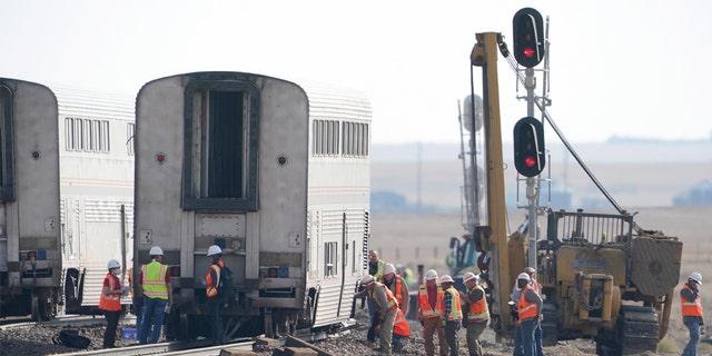 Các công nhân kiểm tra một toa tàu, thứ Hai, ngày 27 tháng 9 năm 2021, từ một chuyến tàu Amtrak trật bánh vào thứ Bảy, gần Joplin, Mont.
