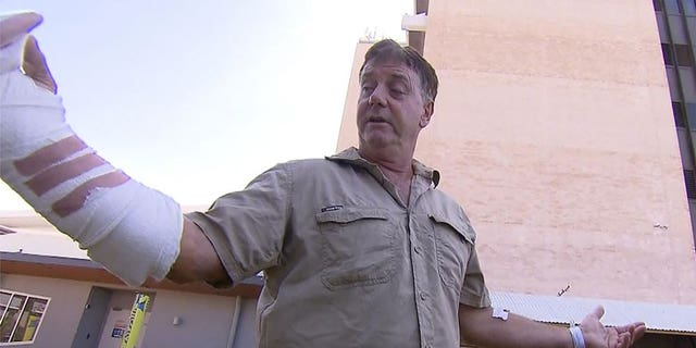 """In this image made from a video, Australian wildlife tour operator Sean Dearly is interviewed in Darwin, Australia, Tuesday, Sept. 28, 2021. Dearly said he was lucky to escape more serious injury or even death when a crocodile lunged from a river and clamped his hand in its jaws. Dearly was attacked on Monday on the Adelaide River, which is renowned for its """"jumping crocodiles,"""" large crocodiles that rise vertically from the water to snatch chicken carcasses dangled from long poles extended from tourist cruise boats. (CHANNEL 9 via AP)"""