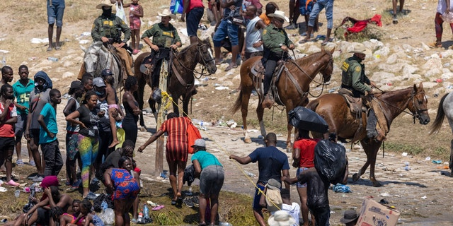 Mounted U.S. Border Patrol agents watch Haitian immigrants on the bank of the Rio Grande in Del Rio, Texas, il sett. 20, 2021, as seen from Ciudad Acuna, Messico. (Photo by John Moore/Getty Images)