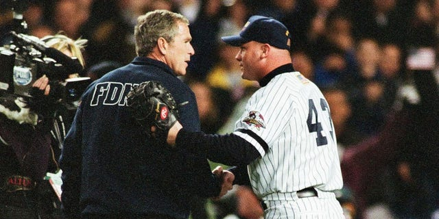 President George W. Bush shakes hands with New York Yankees wide receiver Todd Greene before pitching the first pitch before Game 3 of the World Series between the Arizona Diamondbacks and the New York Yankees on October 30, 2001 at the Yankee Stadium in the Bronx, New York York.  (Photo by Sporting News via Getty Images via Getty Images)