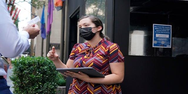 九月. 13, 2021: Maitre d' Susanne McDonald checks guests' proof of vaccination at a restaurant in midtown Manhattan in New York.