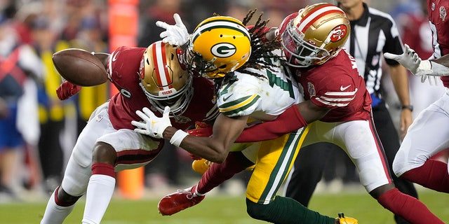 Green Bay Packers wide receiver Davante Adams, middle, cannot catch a pass between San Francisco 49ers cornerback Jimmie Ward, left, and defensive back Emmanuel Moseley during the second half of an NFL football game in Santa Clara, Calif., Sunday, Sept. 26, 2021.