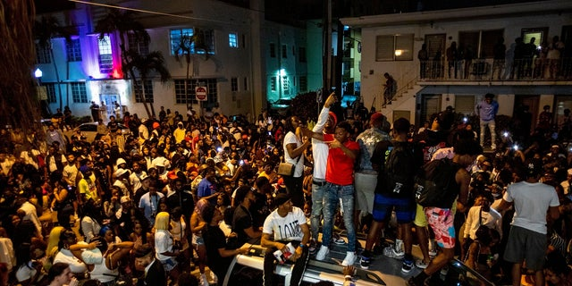 FILE - In this Sunday, March 21, 2021, file photo, crowds defiantly gather in the street while a speaker blasts music an hour past curfew in Miami Beach, Fla. (Daniel A. Varela/Miami Herald via AP, File)