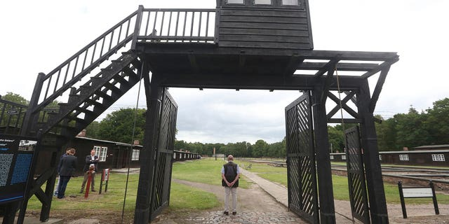 The wooden main gate leads into the former Nazi German Stutthof concentration camp in Sztutowo, Poland. An elderly secretary of the former SS commandant of Stutthof was going on trial Thursday in Germany on charges of more than 11,000 counts of accessory to murder. (AP Photo/Czarek Sokolowski, file)