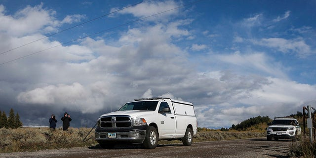 """An unmarked coroner's vehicle, front, drives past members of the media waiting in the Spread Creek area of the Bridger-Teton National Forest, just east of Grand Teton National Park off U.S. Highway 89 in Wyoming, Sunday, Sept. 19, 2021. Authorities say a body discovered is believed to be Gabrielle """"Gabby"""" Petito. The FBI said the body was found by law enforcement agents who had spent the past two days searching campgrounds. (AP Photo/Amber Baesler)"""