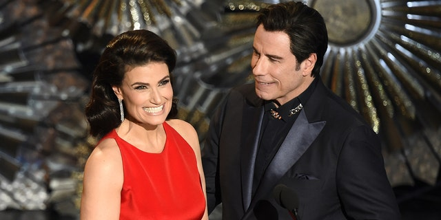 John Travolta (R) and Idina Menzel present an award on stage at the 87th Oscars February 22, 2015 in Hollywood, California.