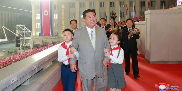 """उत्तर कोरियाई सरकार द्वारा प्रदान की गई इस तस्वीर में, उत्तर कोरिया के नेता किम जोंग उन, उत्तर कोरिया के प्योंगयांग में किम इल सुंग स्क्वायर में राष्ट्र की 73 वीं वर्षगांठ के जश्न के दौरान गुरुवार, 9 सितंबर, 2021 को बच्चों के साथ चलते हैं। स्वतंत्र पत्रकार थे उत्तर कोरियाई सरकार द्वारा वितरित इस छवि में दर्शाए गए कार्यक्रम को कवर करने के लिए एक्सेस नहीं दिया गया है।  इस छवि की सामग्री प्रदान की गई है और इसे स्वतंत्र रूप से सत्यापित नहीं किया जा सकता है।  स्रोत द्वारा प्रदान की गई छवि पर कोरियाई भाषा वॉटरमार्क पढ़ता है: """"केसीएनए"""" जो कोरियन सेंट्रल न्यूज एजेंसी का संक्षिप्त नाम है।  (कोरियाई केंद्रीय समाचार एजेंसी/एपी के माध्यम से कोरिया समाचार सेवा)"""