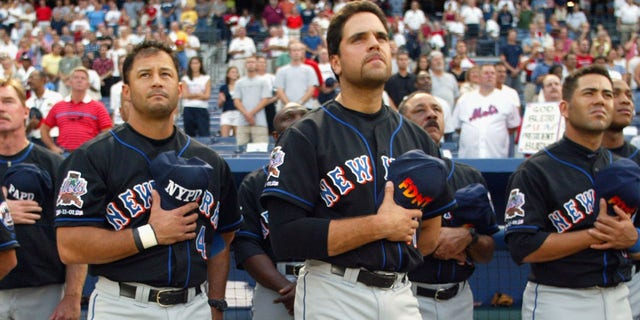 # 47 left fielder Joe McEwing, # 4 John Valentin shortstop, # 31 wide receiver Mike Piazza, # 13 third baseman Edgardo Alfonzo and # 20 Mets right fielder Jeromy Burnitz. New Yorkers hold their FDNY and NYPD hats over their hearts during the national anthem ahead of Game 2 of an MLB brace against the Atlanta Braves on September 11, 2002 at Turner Field in Atlanta, Georgia.  The Mets shut out the Braves 5-0.