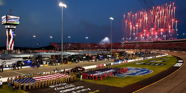 RICHMOND, VIRGINIA - SEPTEMBER 11: Fireworks erupt as members of the military and first responders hold the American and 9/11 Never Forget flag during pre-race ceremonies prior to the NASCAR Cup Series Federated Auto Parts 400 Salute to First Responders at Richmond Raceway on September 11, 2021 in Richmond, Virginia. (Photo by Jared C. Tilton/Getty Images)