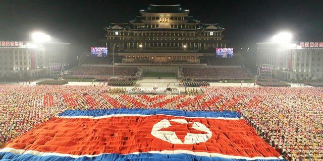 """उत्तर कोरियाई सरकार द्वारा प्रदान की गई इस तस्वीर में, उत्तर कोरिया के प्योंगयांग में किम इल सुंग स्क्वायर में गुरुवार तड़के, 9 सितंबर, 2021 को राष्ट्र की 73 वीं वर्षगांठ के उत्सव के दौरान एक विशाल उत्तर कोरियाई ध्वज प्रदर्शित किया गया है। स्वतंत्र पत्रकारों को नहीं दिया गया था उत्तर कोरियाई सरकार द्वारा वितरित इस छवि में दर्शाए गए कार्यक्रम को कवर करने के लिए पहुंच।  इस छवि की सामग्री प्रदान की गई है और इसे स्वतंत्र रूप से सत्यापित नहीं किया जा सकता है।  स्रोत द्वारा प्रदान की गई छवि पर कोरियाई भाषा वॉटरमार्क पढ़ता है: """"केसीएनए"""" जो कोरियन सेंट्रल न्यूज एजेंसी का संक्षिप्त नाम है।  (कोरियाई केंद्रीय समाचार एजेंसी/एपी के माध्यम से कोरिया समाचार सेवा)"""