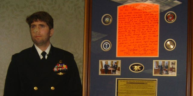 Jason Redman stands in uniform beside the sign that was posted outside his hospital room.