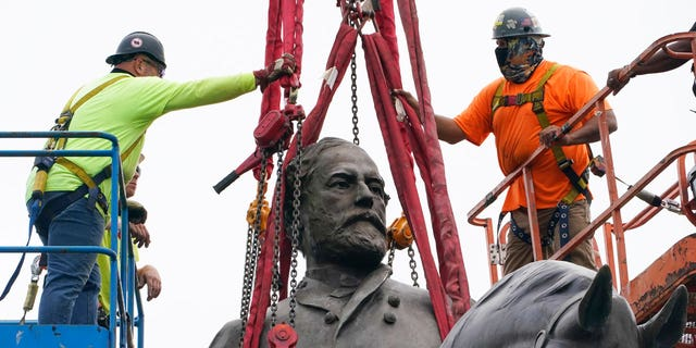 Crews work to remove one of the country's largest remaining monuments to the Confederacy, a towering statue of Confederate General Robert E. Lee on Monument Avenue, Wednesday, Sept. 8, 2021, in Richmond, Va. (AP Photo/Steve Helber, Pool)