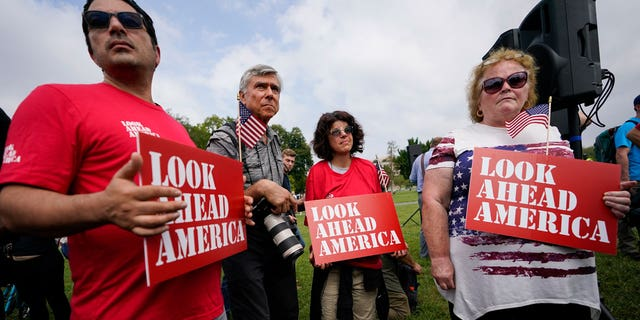 """Demonstrators hold signs near members of the media before a rally near the U.S. Capitol in Washington, Saturday, Sept. 18, 2021. The rally was planned by allies of former President Donald Trump and aimed at supporting the so-called """"political prisoners"""" of the Jan. 6 insurrection at the U.S. Capitol. (AP Photo/Brynn Anderson)"""